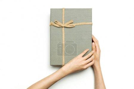 女人的手拿着一个白色的灰色礼品盒.