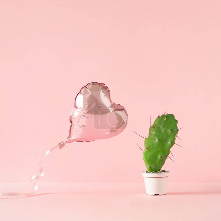 Heart shaped foil balloon with cactus plant on pink background. Creative valentine day concept.
