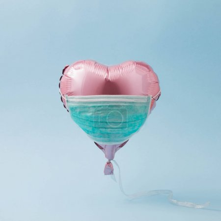 Pink balloon heart with face protective mask. COVID-19 concept. new Corona virus infection(novel coronavirus disease). Pandemic infectious background.