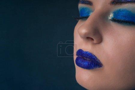 一个美丽的女孩的肖像与蓝色化妆和她的嘴唇上的火花