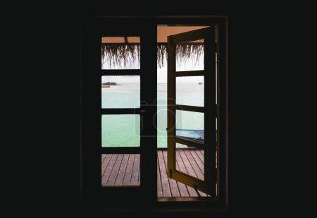 从小屋的部分打开的窗口鸟瞰海景