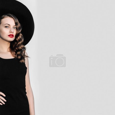 高时尚户外全长幅画像,优雅的女人,在黑色的帽子和衣服站在白色柱子后面。黑色与红色的嘴唇女子复古风格肖像